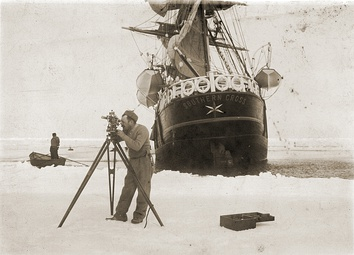 Expedition commander Carsten Borchgrevink taking a theodolite reading in front of the Southern Cross, 1899
