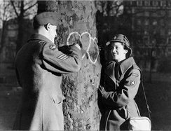 Canadian couple (her, a member of the Canadian Women's Army Corps, him, a member of the Canadian Air Force) chalking hearts onto a tree on Valentine's Day 1944