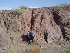 Salmon-colored fault gouge and associated fault separates two different rock types on the left (dark gray) and right (light gray). From the Gobi of Mongolia.