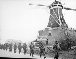 Canadian troops pass a windmill in Rijssen-Holten, April 1945.