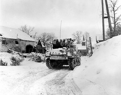 Members of 'I' Company of the 3rd Battalion, 16th Infantry Regiment ride on a tank during their advance on the town of Schopen, Belgium, 21 January 1945.