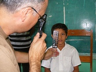 U.S. Navy optometrist Cmdr. Louis Perez uses a retina scope and lens rack to check the eyes of 9-year old Sergio Colochos during the Beyond the Horizon humanitarian assistance exercise in Honduras.