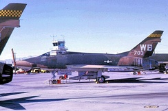 "The Nellis control tower behind a 4536th F-100D (""WB"" tail code). In July 1968 the first tail codes appeared on Nellis-based aircraft:[30] ""WC"" (4537th F-105), ""WD"" (4538th F-4C), & ""WF"" (4539th F-111)."
