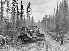 A caterpillar tractor with grader widens the roadway of the Alaska Highway, 1942