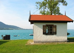 A small lakeside building showing a single window in a white wall below a sloping red roof