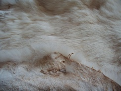 Tanned rabbit pelt. The fur has been left on, apart from small patches exposing leather.
