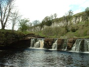 Wain Wath Force, near Keld, with the limestone cliffs of Cotterby Scar in the background.