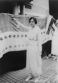 Alice Paul stands victorious before the Women's Suffrage Amendment's ratification banner.