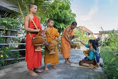 Buddhist monks collect alms in Si Phan Don, Laos. Giving is a key virtue in Buddhism.