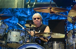 "Ian Paice (pictured in 2017). Ranked number 21 in Rolling Stone's 100 Greatest Drummers list, his magazine entry states, ""without Deep Purple's only continuous member, there would be no heavy metal drumming.""[148]"