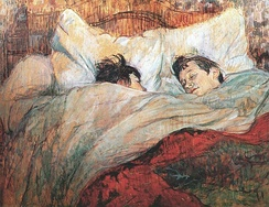 A painting by Henri de Toulouse-Lautrec of two short-haired women in a massive bed, covered to their chins in blankets under a red top cover. One woman is looking sleepily at the other.