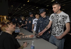 Members of Bowling for Soup signing autographs for sailors aboard the carrier USS John C. Stennis.
