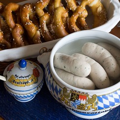 Traditional Weisswurst meal, served with sweet mustard and soft pretzels