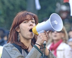 A woman using a small handheld electric megaphone at a demonstration in Portugal. Electric megaphones use a type of horn loudspeaker called a reflex or reentrant horn.