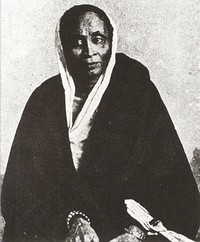 An elderly Bengali woman in white sati and a dark wrapper