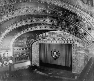 The Proscenium arch of the theatre in the Auditorium Building, Chicago. It is the frame decorated with square tiles that forms the vertical rectangle separating the stage (mostly behind the lowered curtain) from the auditorium (the area with seats).