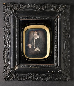 A framed daguerrotype surrounded by a passe-partout