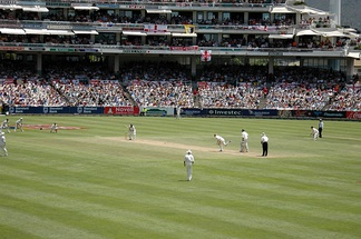 A Test match between South Africa and England in January 2005. The two men wearing black trousers are the umpires. Test cricket is played in traditional white clothes and usually with a red ball – a pink ball in Day/Night Tests.