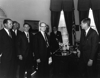 William H. Pickering, (center) JPL Director, President John F. Kennedy, (right). NASA Administrator James E. Webb (background) discussing the Mariner program, with a model presented.