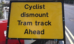 A sign advising cyclists to dismount due to tram tracks. Tram tracks pose a hazard for cyclists, as their wheels may get caught in the track.