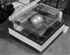 A stack of square metal plates with a side about 10 inches. In the 3-inch hole in the top plate there is a gray metal ball simulating Pu.