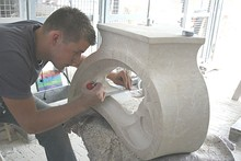 An apprentice carving a block