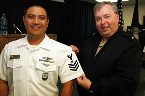 Rear Admiral Terry McCreary presenting a rating insignia of a mass communication specialist first class (MC1).