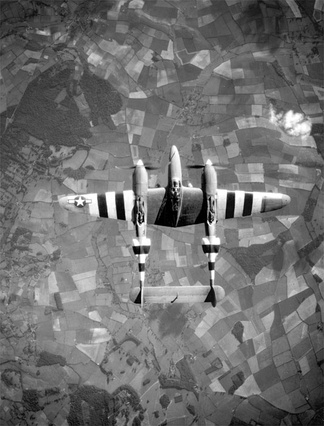 A USAAF photo-reconnaissance Lockheed F-5 Lightning in flight over Europe circa June 1944. It is marked with invasion stripes to help Allied troops clearly identify it as an Allied plane.