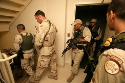 Border Patrol agents—including the Border Patrol Tactical Unit (BORTAC) and Laredo Sector Special Response Team—conduct a room-by-room search of a New Orleans hotel following Hurricane Katrina