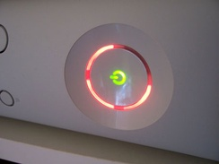 "Three red lights on the Xbox 360's ring indicator representing a ""General Error requiring service of the Console or Power Adapter,"" commonly nicknamed the ""Red Ring of Death."""