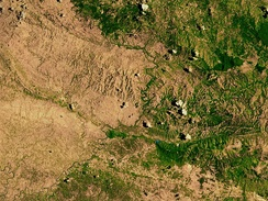 A satellite image of the border between the denuded landscape of Haiti (left) and the Dominican Republic (right), highlighting the deforestation on the Haitian side