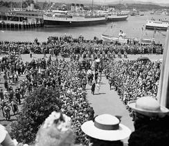 A crowd in Victoria, British Columbia watch King George VI and his royal consort, Queen Elizabeth coming up the walkway during their 1939 royal tour of Canada.
