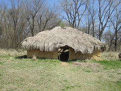 A reconstructed house. Grass-thatched roofs were typical of the later, historic Wichita and Caddo, but their houses were round with high-pitched roofs.