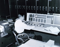 A meteorologist at the console of the IBM 7090 in the Joint Numerical Weather Prediction Unit. c. 1965