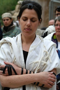 A Jewish woman prays with a tallit and tefillin.
