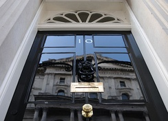 "The door of 10 Downing Street, with ""First Lord of the Treasury"" inscribed on the letterbox as the addressee for post."