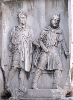 A Parthian (right) wearing a Phrygian cap, depicted as a prisoner of war in chains held by a Roman (left); Arch of Septimius Severus, Rome, 203 AD