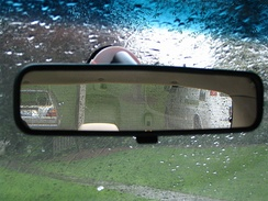Rear-view mirror showing cars parked behind the vehicle containing the mirror