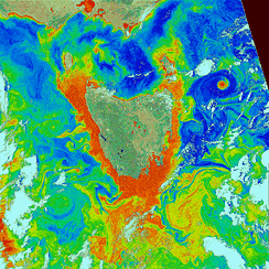 An image of Tasmania and surrounding waters using density slicing to show phytoplankton concentration. The ocean color as captured by the satellite image is mapped to seven colors: Yellow, orange and red indicate more phytoplankton, while light green, dark green, light blue and dark blue indicate less phytoplankton; land and clouds are depicted in different colors.
