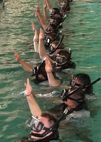 "Search and Rescue students give the ""I am all right"" signal to let the SAR instructors know that they are ready for further instructions at the pool on board Naval Station San Diego."
