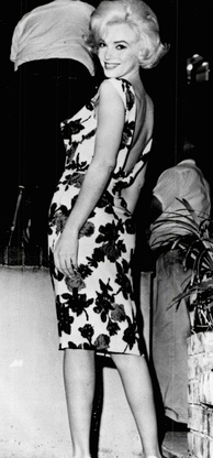 Monroe wearing a form-fitting white dress with flowers and an open back. She is standing and smiling over her shoulder at the camera.