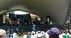 Performers on an outdoor stage with shell-shaped overhang before an audience seated in the sun.