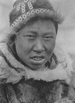 A Hooper Bay Askinarmiut boy poses wearing a circular cap (uivqurraq) and fur parka, photograph by Edward S Curtis (1930).[27]