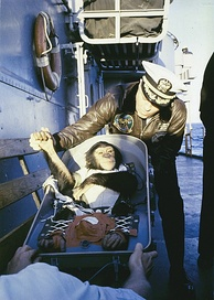 "A ""hand shake"" welcome. After his flight on a Mercury-Redstone rocket, chimpanzee Ham is greeted by the commander of the recovery ship, USS Donner (LSD-20)."