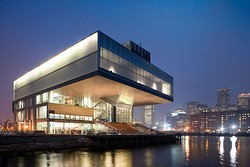 Oblique view of the Institute of Contemporary Art on Boston's waterfront at night with the city in the background.