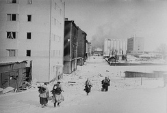 Four Finnish soldiers, with their backs shown, are retreating to the demarcation line after the ceasefire came into effect. The city of Vyborg looks empty and smoke is rising in the background.