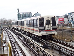 An S-series northbound train at Lawrence East station. Note the slab between the running rails.
