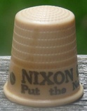 "An off-white thimble, with the visible black lettering, ""NIXON/Put the ne ..."