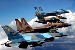 A flight of Aggressor F-15 Eagles and F-16 Fighting Falcons fly in formation. The jets are assigned to the 64th and 65th Aggressor squadrons at Nellis Air Force Base. Identified aircraft are F-16C Block 32C 86-251; Block 25E 84-1299; F-15C-27-MC 80-0010 and F-15D-39-MC 85-129.