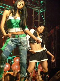 Two women dancing, wearing colourful, trendy clothing and with exposed midriffs